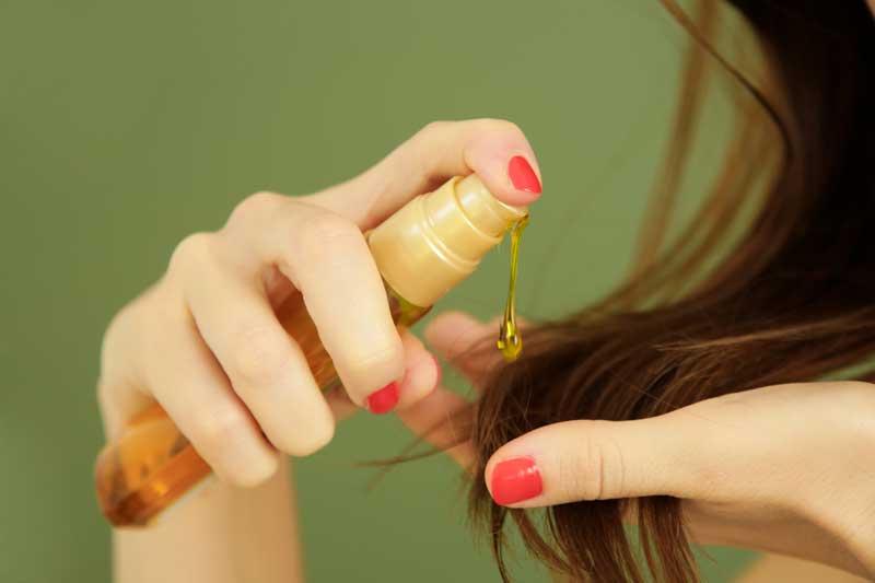 chica poniendo aceite en cabello